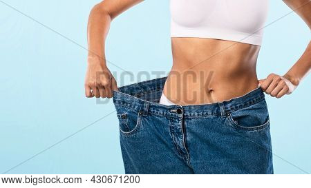 Closeup Of Skinny Fit Woman Pulling Large Loose Jeans