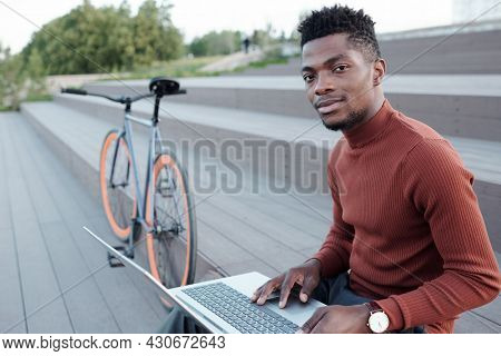 Young contemporary white collar worker using laptop in urban environment