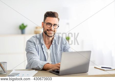 Portrait Of Freelancer Man Sitting At Desk With Laptop Computer At Home Office, Smiling At Camera, F