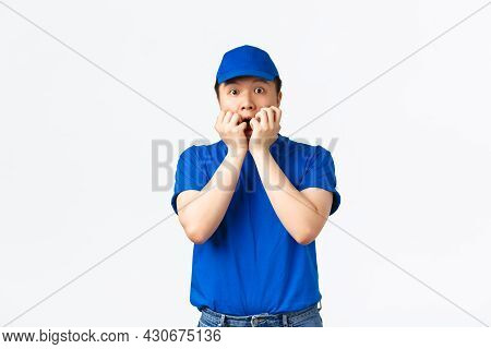 Portrait Of Startled Frightened Asian Delivery Man, Gasping Holding Hands Over Mouth, Biting Fingern