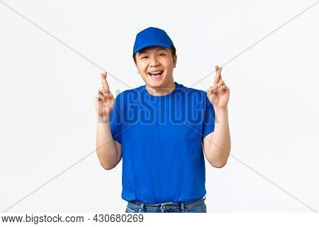 Portrait Of Excited Hopeful Asian Guy With Braces, Delivery Man In Blue Uniform Hope And Make Wish,