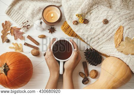Hands Holding Warm Cup Of Tea On Background Of Autumn Leaves, Pumpkin, Cozy Sweaters, Burning Candle
