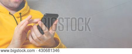 Unrecognizable Caucasian Man In Yellow Sweatshirt Is Searching In Cell Phone. Close-up. Black Mobile