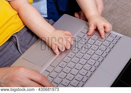 Small Babys Hands On Laptop Keyboard. Top View. Son Helps Daddy Blogger Work From Home. Dad Sitting