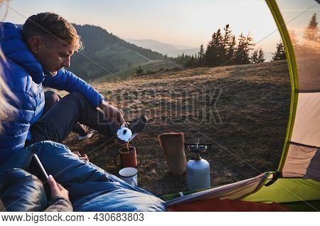 Handsome Man Traveler Sitting On Grassy Hill Near Camp Tent And Pouring Hot Drink Into Cup. Male Hik