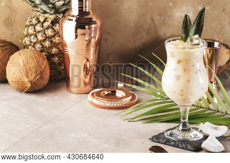 Pina Colada Cocktail On Sand Beige Background With Tropical Fruits And Copper Bar Tools, Negative Sp