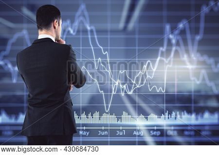 Back View Of Attractive Young European Businessman On Blurry Office Interior Background Looking At B