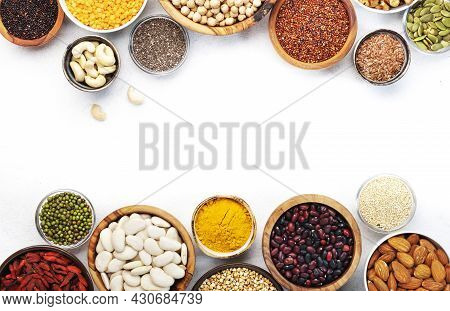 Set Of Superfoods, Legumes, Cereals, Nuts, Seeds In Bowls On White Table. Copy Space, Top View