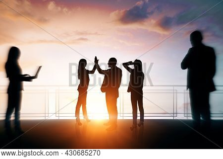 Group Of Businesspeople With Hi-five Gesture Standing On Sunset Background. Success, Teamwork And Co