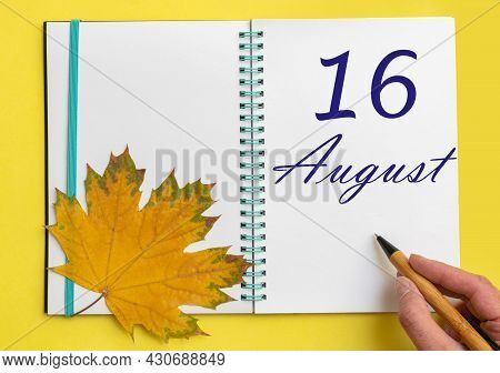 16th Day Of August. Hand Writing The Date 16 August In An Open Notebook With A Beautiful Natural Map