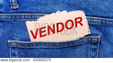 In The Back Pocket Of The Jeans There Is A Brown Piece Of Paper With The Text Vendor