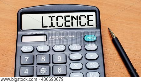 On A Wooden Table There Is A Black Pen And A Calculator With The Text Licence. Business Concept