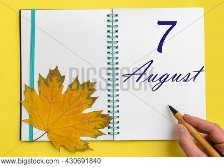 7th Day Of August. Hand Writing The Date 7 August In An Open Notebook With A Beautiful Natural Maple