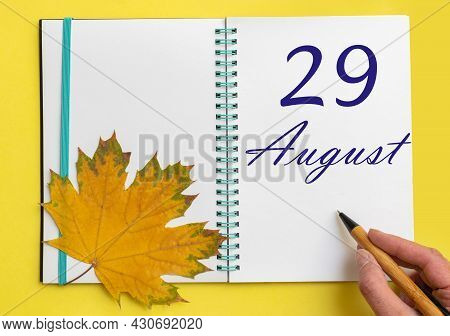 29th Day Of August. Hand Writing The Date 29 August In An Open Notebook With A Beautiful Natural Map