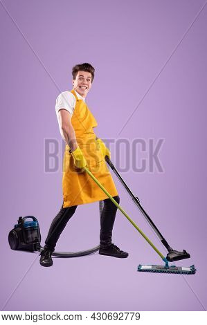 Full Body Crazy Young Man In Yellow Apron And Gloves Smiling And Looking At Camera While Tidying Flo