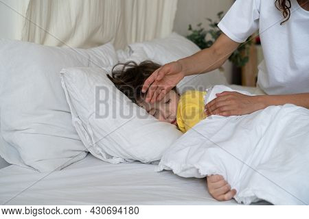 Mother Checking Temperature Of Sick Son Lying Sleep In Bed With Fever From Influenza Or Coronavirus