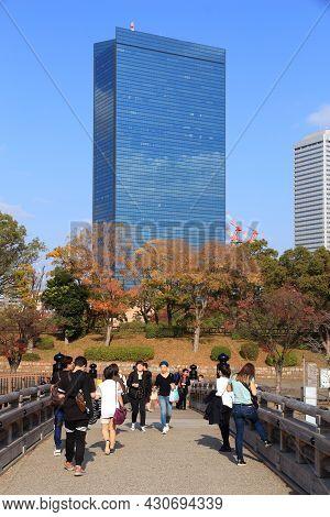 Osaka, Japan - November 22, 2016: People Walk By Crystal Tower Skyscraper In Osaka, Japan. Crystal T