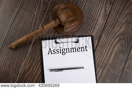 Assignment Text On The Paper With Gavel On The Wooden Background