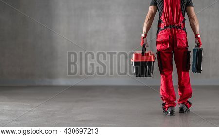 Lower Body Part Of Professional Caucasian Worker Wearing Red Uniform With Toolboxes In His Hands. Le