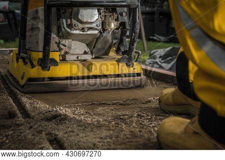 Professional Soil Compactor Job Close Up. Building Concrete Tiles Garden And Patio Pathway. Powerful