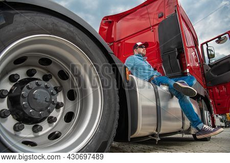 Caucasian Semi Truck Driver In His 30s And His Brand New Red Tractor Truck. Heavy Duty Transportatio