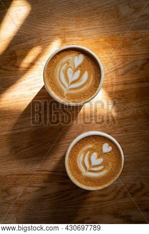 Coffee On Wooden Background. Two Cups Of Cappuccino With Latte Art On Brown Table With Sunbeam. Fres