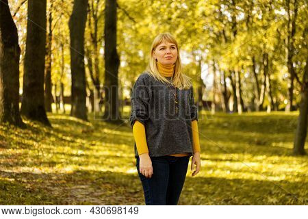 Defocus Serious Blond 40s Woman Standing In Yellow Autumn Park. Happy Beautiful Lady. Women Wearing