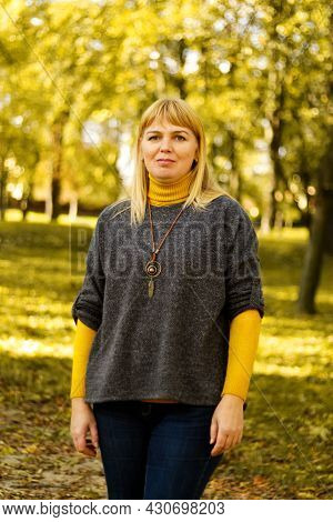 Defocus Light Smiling Blond 40s Woman Standing In Yellow Autumn Park. Happy Beautiful Lady. Women We