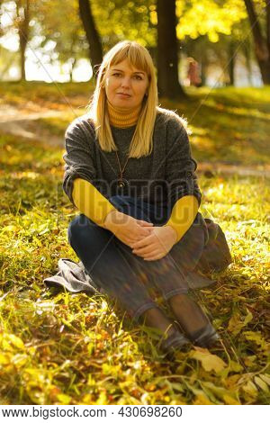 Defocus Smiling Blond 40s Woman Seating In Yellow Autumn Park. Happy Beautiful Lady. Women Wearing G
