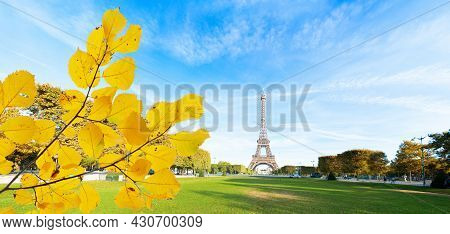 Paris Eiffel Tower Over Green Grass Lane In Paris, France. Web Banner Format. Eiffel Tower Is One Of