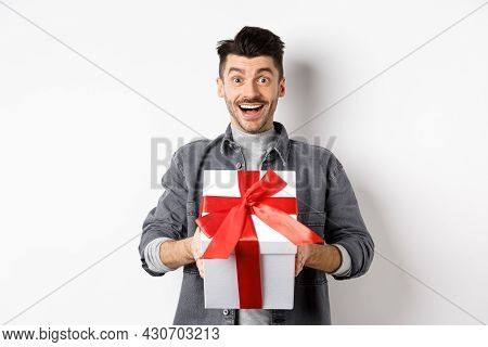 Surprised Young Man Smiling Excited, Holding Big Gift Box On Valentines Day Holiday, Receive Surpris