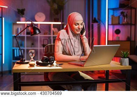 Pretty Arabian Woman Talking On Mobile And Typing On Laptop While Sitting At Desk During Evening Tim