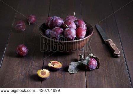 Still Life With Fresh Ripe Plums In A Clay Ceramic Bowl And A Knife On A Dark Wooden Surface. Rustic