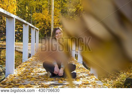 Hipster Young Woman Sitting  And Meditates In Lotus Position (padmassana), Zen Like On Autumn Sunny