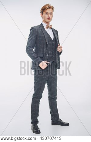 Full length portrait of handsome blond young man poses in elegant classic suit and bow-tie on white background.  Men's beauty, fashion.