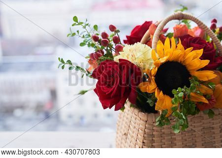 A Basket With Beautiful Autumn Flowers Made Of Red Roses, Sunflowers And Green Leaves. The Concept O