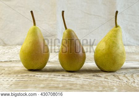One Juicy Ripe Yellow Pear On Grey Wooden Background Close-up Front View Still Life