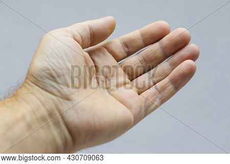 The Outstretched Hand Of A Man On A Light Background.