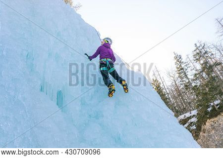 Female Ice Climber In Traction Position, Swinging Ice Axes Overhead And Planting The Pick In The Ice
