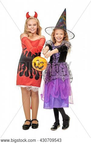 Two happy girls in costumes of a witchs smiling  holding pumpkin basket on a yellow background. Halloween celebration. Fancy dress costumes for children.