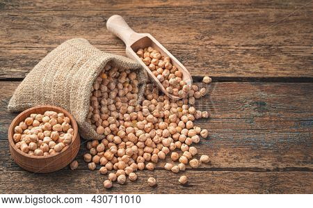 Dry, Raw Chickpeas In A Linen Bag, A Wooden Scoop And A Bowl On A Wooden Background.