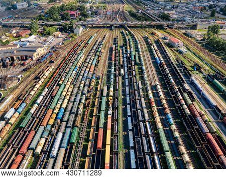 Aerial Photo Of Lots Of Various Wagons: Tanks, Platforms, Dump Trucks Stay On Railways At Terminal.