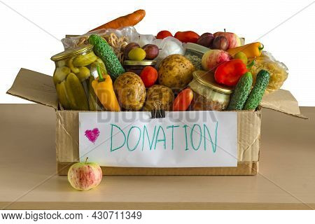 Box With Food Donations On Light Table Is Isolated On White Background. Grocery Set To Help Those In