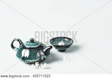 Green Tea In A Dark Turquoise Clay Teapot And Small Cup Decorated With White Flowers On Pastel Backg