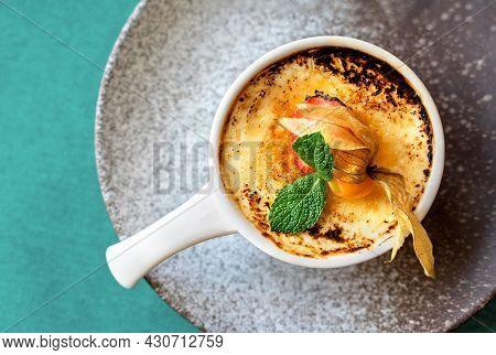 Delicious Creme Brulee Dessert With Caramelized Cane Sugar, Fresh Berries And Mint Leaves In White C