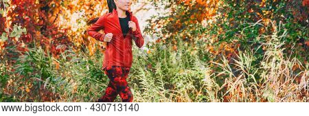Outdoor exercise healthy runner running outside in autumn foliage landscape banner. Jogging woman in forest park panoramic. Girl athlete runner wearing red sportswear running jacket and leggings.