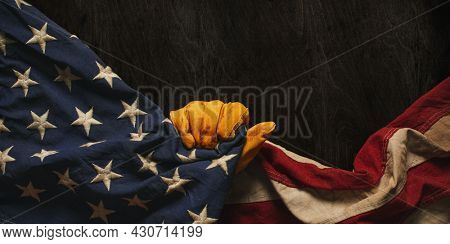 Worn work glove holding US American flag. Made in USA, American workforce, blue collar worker, or Labor Day concept.