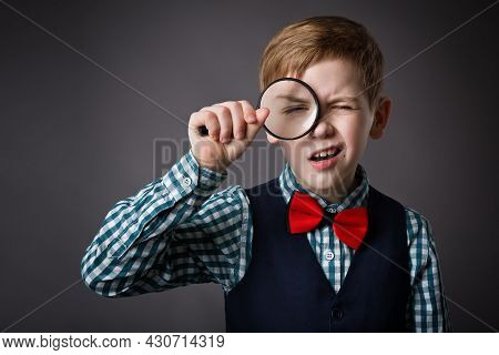 Little Kid Looking Through Magnifying Glass Lens. Funny Surprised Child Holding Loupe. School Boy In