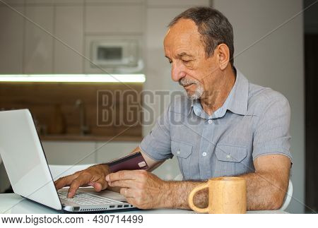 Trendy Mature Man Is Working From Home With Laptop Sitting At The Table In His Kitchen, Buying Somet