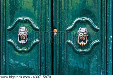 Door Knocker Like Antique Head On The Entrance Of A House, Old Ornate Metal Door Handle, Italy